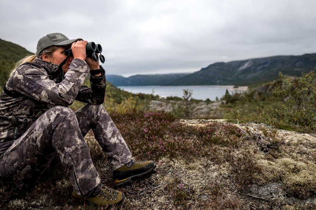 Woman in camouflage looking at the Norwegian landscape with binoculars