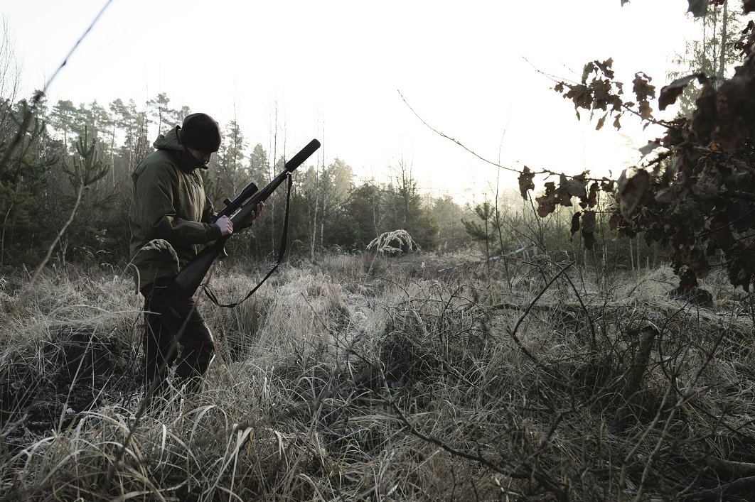 Hunter with rifle and silencer in foggy forest