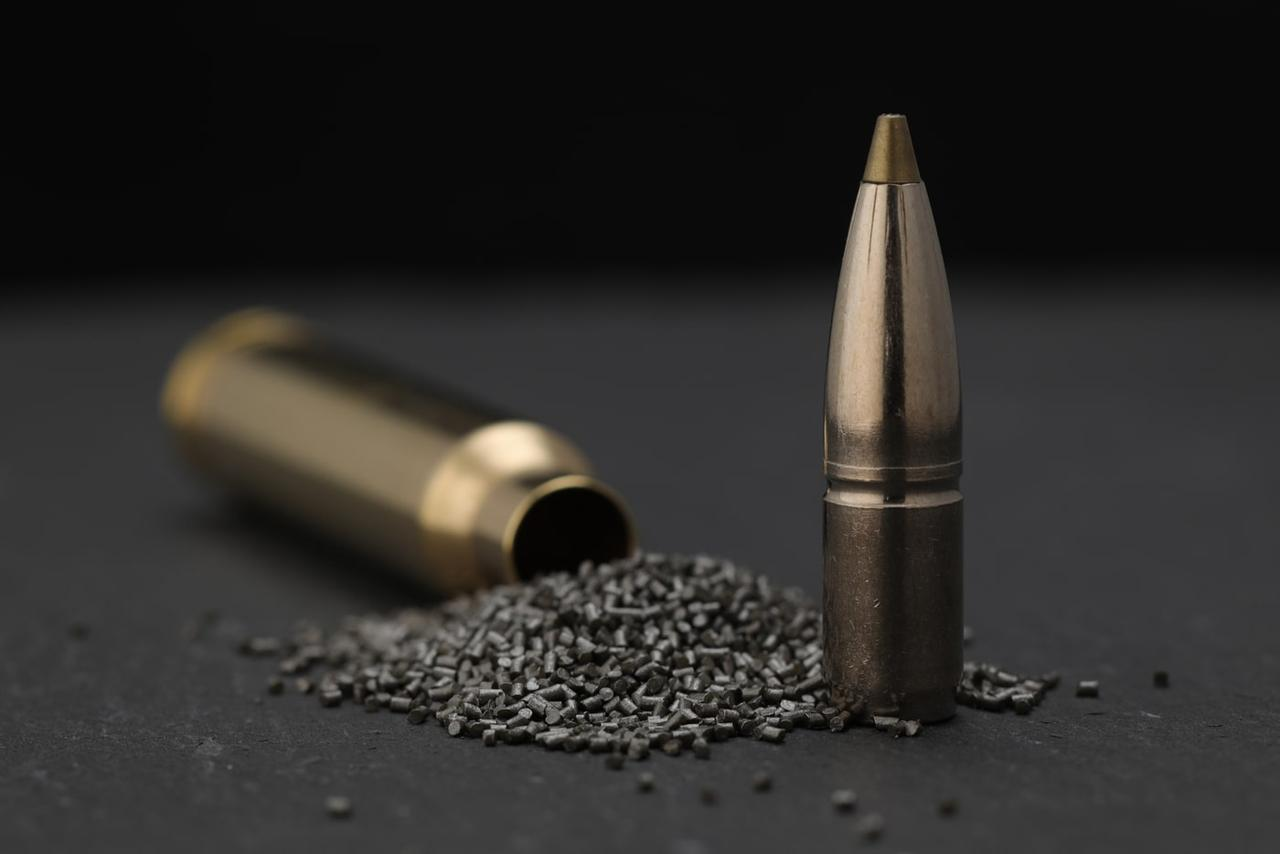 An image of a rifle cartridge, divided into its essentials components such as case, propellant powder and projectile