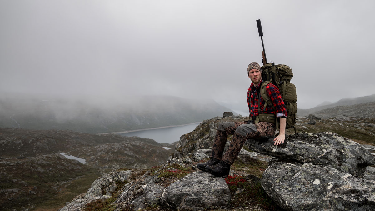 A hunter in camouflage clothes sits on rock with rifle on his back