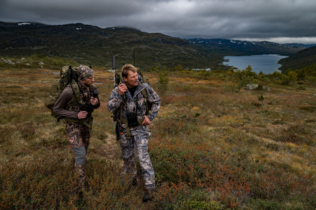 Two hunters in camouflage clothing stand in the wilderness of Norway