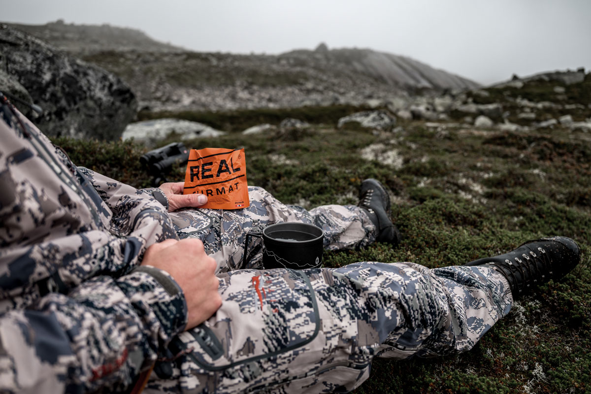 A hunter eats small refreshments and drinks from the thermos