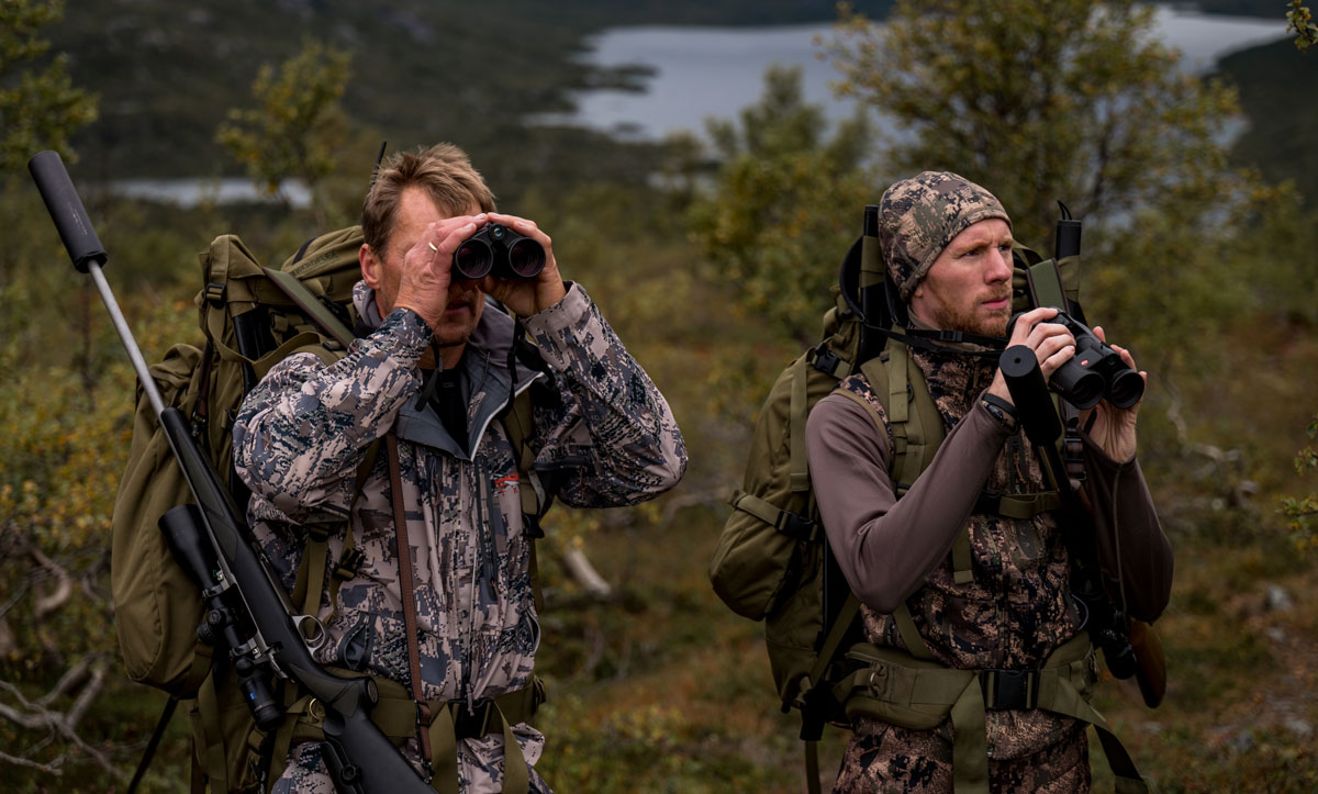Two hunters in camouflage clothing go through a rocky landscape with backpacks